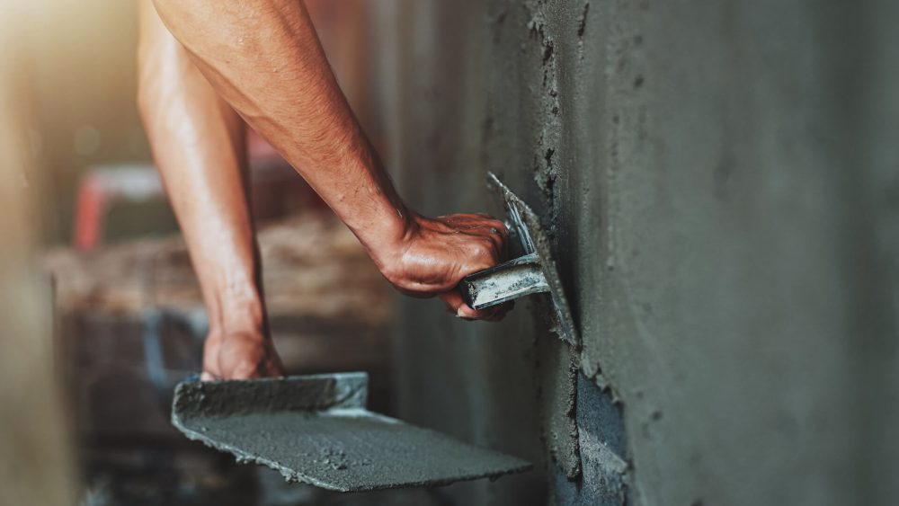closeup-hand-worker-plastering-cement-wall-building-house